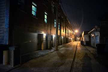 Fototapete - Shadow of a person in a dark scary alley at night
