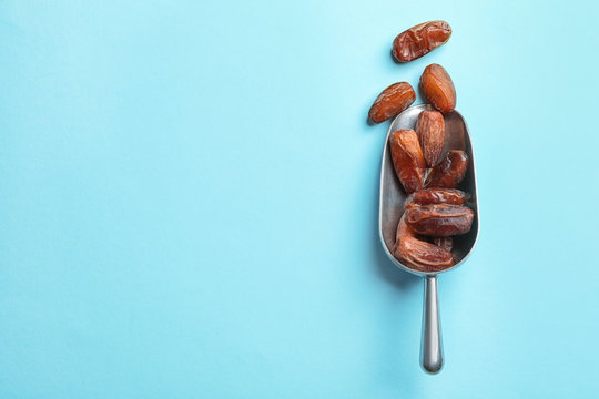 Scoop with sweet dried date fruits on color background, top view. Space for text