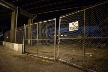 Fotomurales - Dark and scary abandoned area with a fence under a highway city bridge at night in Chicago
