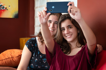 Hispanic teenage girl and her mother taking a selfie at home