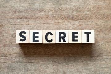 Letter block in word secret on wood background