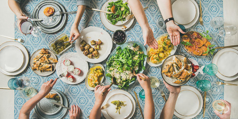 Mediterranean style dinner. Flat-lay of table with salads, starters, pastries over blue table cloth with hands holding drinks, sharing food, top view. Holiday gathering, vegetarian party concept Fototapete