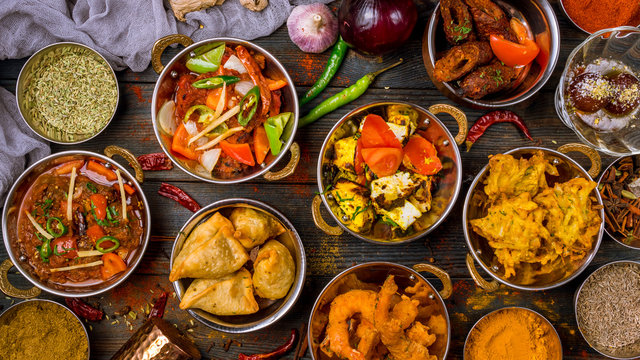 Assorted indian food set on wooden background. Dishes and appetisers of indeed cuisine, rice, lentils, paneer, samosa, spices, masala. Bowls and plates with indian food