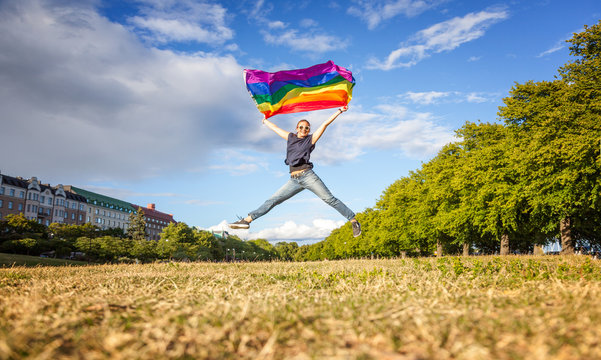 A young happy woman jumps in a summer park with a rainbow flag in her hands, a symbol of LGBT, equal rights and freedoms for people with homosexual orientation.