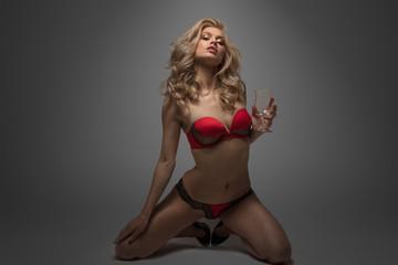 Beautiful blonde in red underwear holding empty glass kneeling on gray background