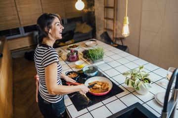 Jonge vrouw die een gezonde maaltijd proeft in de keuken van het huis. Diner maken op keukeneiland staand door inductiekookplaat. Verse groenten bereiden, genieten van kruidenaroma& 39 s. In eten. Passie voor koken. Keto-dieet