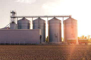 Agricultural silos for soy and  grains sunset shot , trailers in front of object