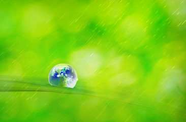 Earth in water drop on green grass with soft bright raining background, Water and Environmental concept , Elements of this image furnished by NASA