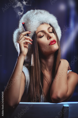Portrait Of The Beautiful Girl Smoking Cigar And Wearing A