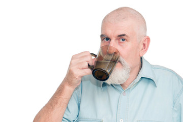 A bearded pensioner drinks tea in the kitchen.