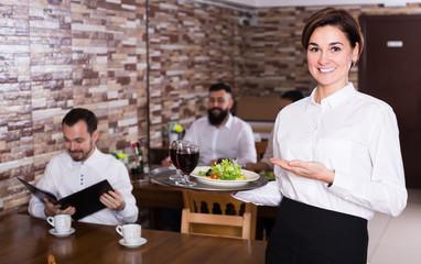 Young female waiter bringing order for visitors