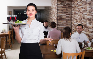 Portrait of smiling woman waiter carrying order