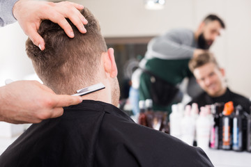 fashionable guy stylist creating haircut for man client at hairdressing salon