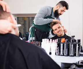 Male hairdresser accurately cutting beard