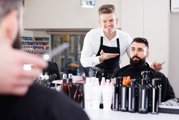 happy guy stylist demonstrating final haircut to client at hairdressing salon