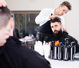 concentrated male stylist creating haircut for man client at hairdressing salon