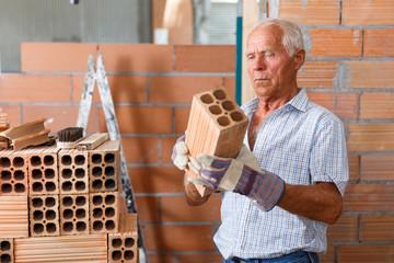 Man checking brick for masonry