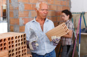 Elderly man with daughter installing brick wall inside