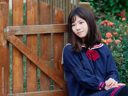 6622fdfd1f3 Outdoor portrait of beautiful young Chinese girl in blue school uniform  japanese style sitting and looking away in flower garden, happy girl,  beauty, ...
