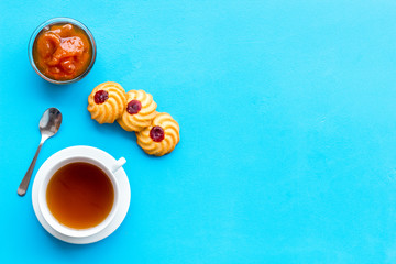 Dessert for evening tea. Cup of tea, fresh homemade cookies on blue background top view copy space
