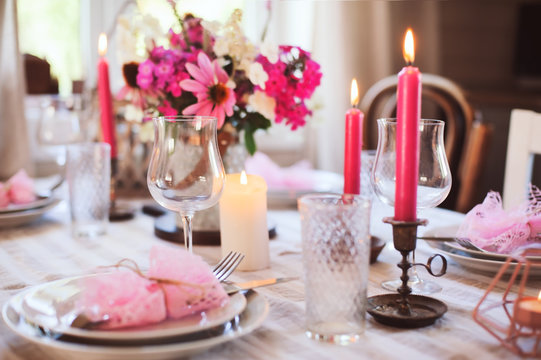 summer cottage kitchen decorated for festive dinner. Romantic table setting with candles and flowers in rustic style.