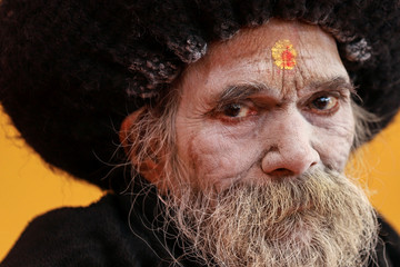 """A Sadhu or a Hindu holy man watches a religious ceremony ahead of the """"Kumbh Mela"""", or the Pitcher Festival, in Prayagraj"""