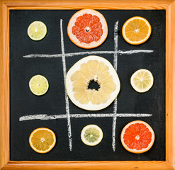 Tic-tac-toe of citrus fruits slice on black chalkboard background, top view. Healthy food concept