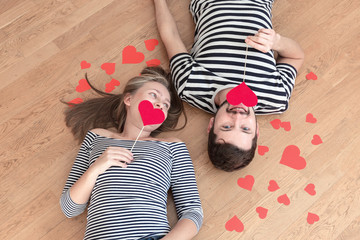 Top view young couple lying on the floor and looking to camera.