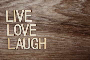 Live Love Laugh text message on wooden background