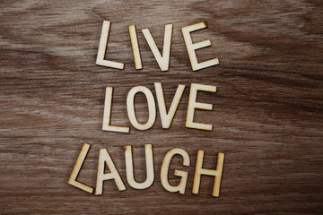 Live Love Laugh text messege on wooden background