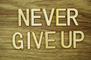 Never Give Up text message on wooden background