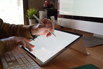 Cropped shot of designer using graphics tablet while working with computer at studio or office