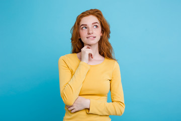 Portrait of happy ginger red hair girl with freckles smiling looking at camera. Pastel blue background. Copy Space