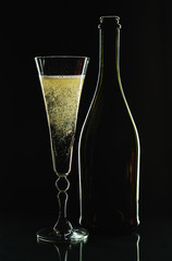 Glass of champagne and bottle on a black background
