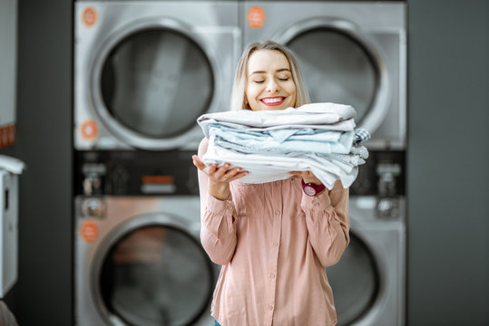 Young woman enjoying clean ironed clothes in the self serviced laundry with dryer machines on the background