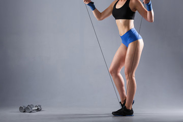 Unidentified young sportswoman holding a jump rope next to a dumbbell on a gray background. Copyspace