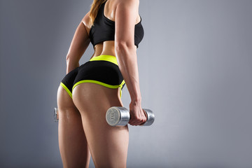 Close-up buttocks of a beautiful young unidentified sports woman with dumbbells in her arms in a sport suit. Concept of a beautiful figure and strength training