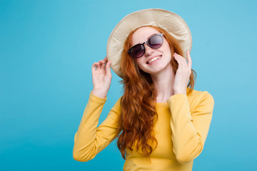 Travel concept - Close up Portrait young beautiful attractive redhair girl wtih trendy hat and sunglass smiling. Blue Pastel Background. Copy space
