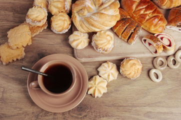 Cup of coffee and sweet pastry on a wooden table