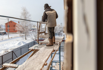 A worker makes mounting a wall on a house