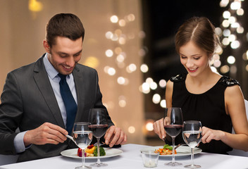 people and leisure concept - smiling couple eating main course with red wine at restaurant over festive lights on background