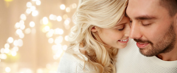 love, valentines day and people concept - close up of happy couple over festive lights on beige background
