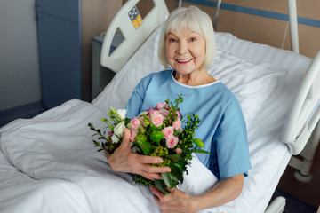 happy recovering senior woman lying in bed with flowers and looking at camera in hospital