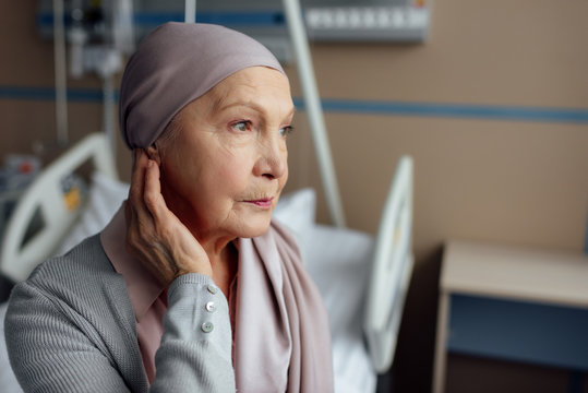 upset senior woman with cancer sitting on bed in hospital