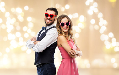 valentines day, love and people concept - happy couple in heart-shaped sunglasses over beige background with festive lights