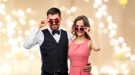 valentines day, love and people concept - happy couple in heart-shaped sunglasses over festive lights background