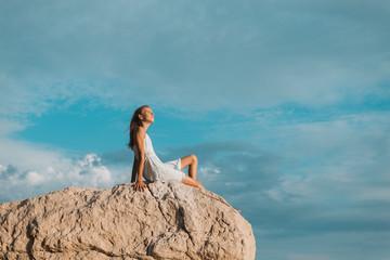 teenager sitzt auf Felsen