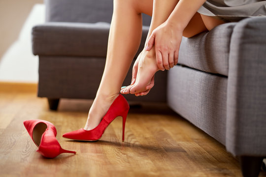 Business Woman taking off sexy red high heels shoes after work and massages painful feet at home on gray couch.