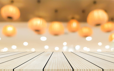 abstract blurred orange color of chinese lantern hang on ceiling and cream wood tabletop perspective for show promote product on display , celebration new year concept
