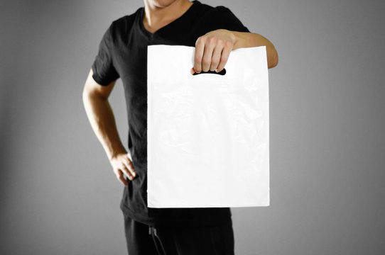 A man holding a white plastic bag. Close up. Isolated on grey background